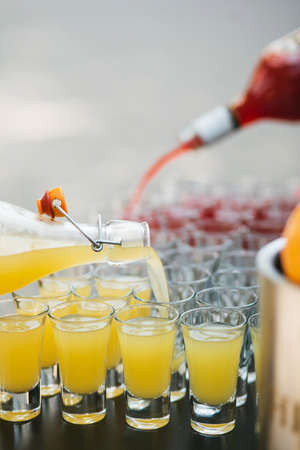 daiquiri alcohol: Many glass shots in which pour from the bottle a yellow and red cocktail, party set Stock Photo