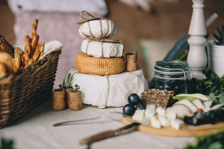 creamery: A pile of cheese heads in a paper, next a sliced cheese, a basket of bread and grapes, wine and plant plugs Stock Photo