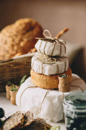 creamery: Pyramid, cake, pile, from cheese heads, near bread, glass jar cork from wine