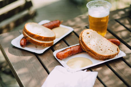 Delicious hot sausages with bread, mustard and beer on a wooden table