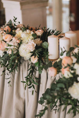 Wedding table decorated with flower bouquets with roses, peonies, eucalyptus and white candles