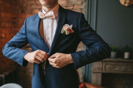 若い新郎、紺のスーツとピンクの蝶ネクタイの男れんが造りの壁、暖炉の背景に彼のジャケットをボタンします。