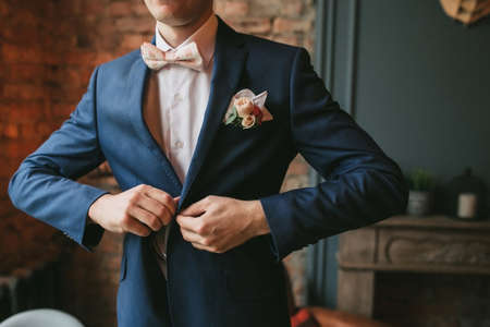 A young groom, man in a blue suit and a pink bow tie button his jacket against the backdrop of a brick wall and a fireplace