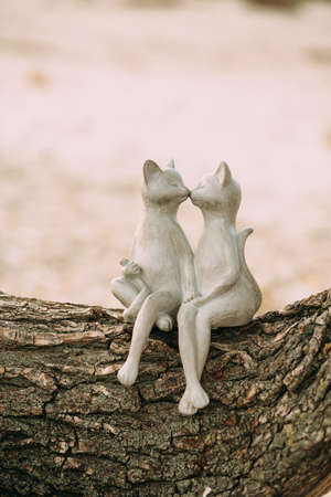 Statues of kissing cats sitting on a log tree bark