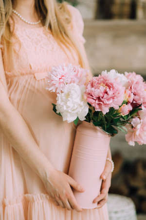 A pregnant woman in a delicate pink dress and a pearl necklace holds a vase of peonies with her hands Stock Photo