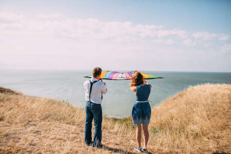 Man and woman in blue over the cliff and the sea, flying a kite 写真素材