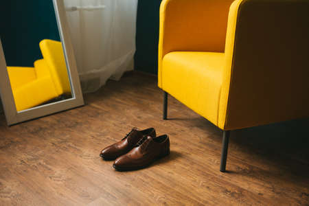 Brown man's shoes brogues on the wooden floor parquet, next to the yellow armchair and mirror. Horizontal