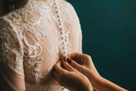 Womens hands fastens with buttons on the back of a beautiful white wedding lace vintage dress close-up, morning training. Stock Photo