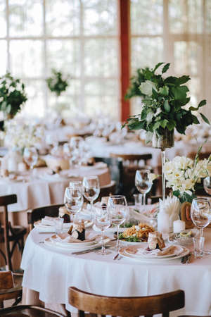 A decorated rustic wedding table with a white tablecloth of porcelain plates with glasses, decorated with bouquets of flowers with banquet dishes and Viennese chairs