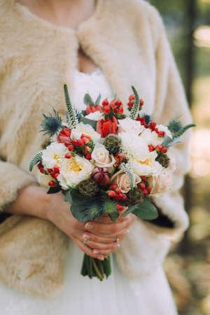 Beautiful elegant autumn wedding bouquet of white roses and red beautiful elegant autumn wedding bouquet of white roses and red flowers in the hands of the mightylinksfo