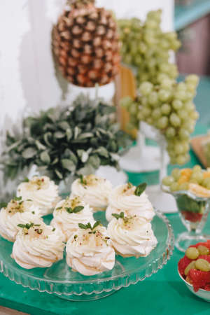 Candy bar. Delicious nature meringue or beze with cream on a glass stand, green grapes, pineapple on a green background. Vertical
