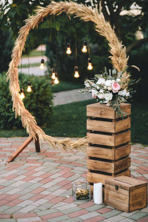 Wedding round arch in rustic style decorated with grass hay field color and retro light bulbs. Near wooden boxes with flower bouquets and candles Standard-Bild - 100075929