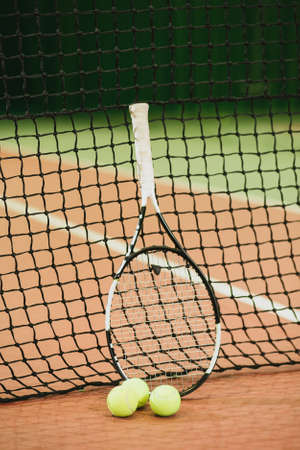 Tennis racket and 3 balls on the tennis court grid close-up. Sports Equipment. Vertical Stock Photo