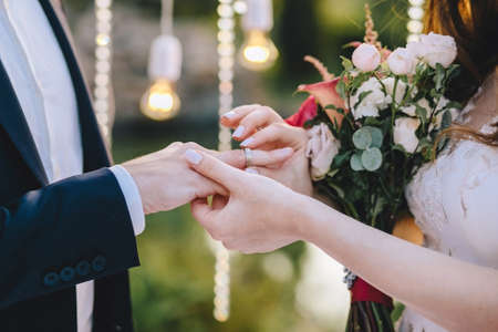 Wedding ceremony. The bride puts on a wedding ring to the groom on a background of light bulbs holding a bouquet in her hands. Horizontal