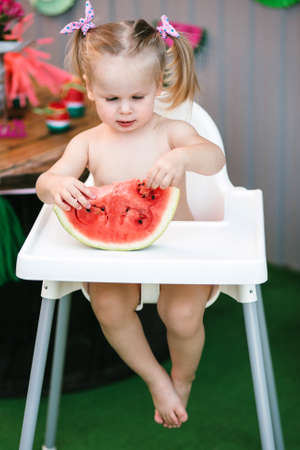 A cute little girl baby blonde touches her hands a juicy piece of watermelon sitting in a children's chair with feet. Vertical