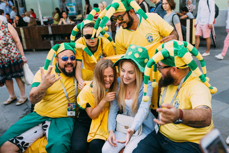 MOSCOW, RUSSIA - JUNE 2018 A group of Brazilian football fans are photographed with Russian girls on the street during the World Cup