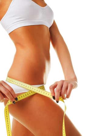 femme se deshabille: Beau corps de la femme sportive avec mesure jaune sur fond blanc