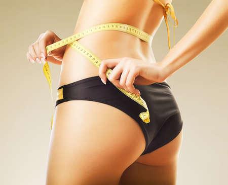 femme se deshabille: minceur femme en culotte avec mesure jaune Banque d'images