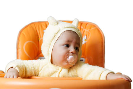 baby on chair: The child sits in a baby chair isolated on white background