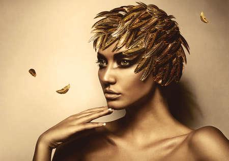 belle brunette: femme en or chapeau de plumes Banque d'images