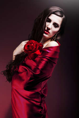 beautiful woman in red fabric with red rose Stock Photo