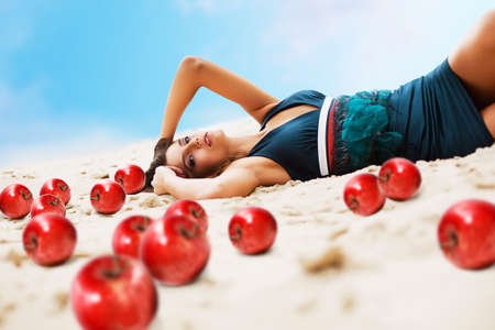 woman with red apples on the sand photo