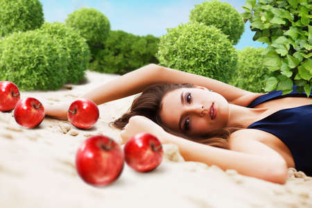 woman with red apples lays on sand in garden photo