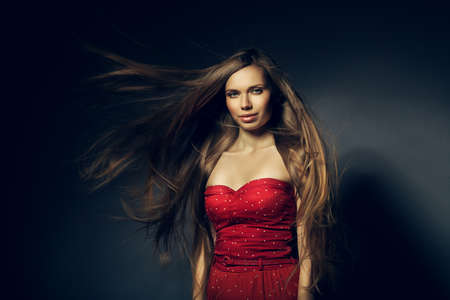beautiful woman in red with long windy hair photo