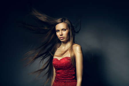pretty woman in red with long windy hair photo