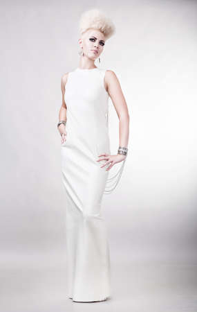blond attractive woman in white dress with creative hairstyle photo