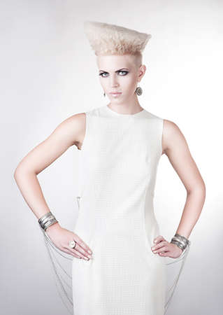 futuristic blond woman in white dress with creative hairstyle photo