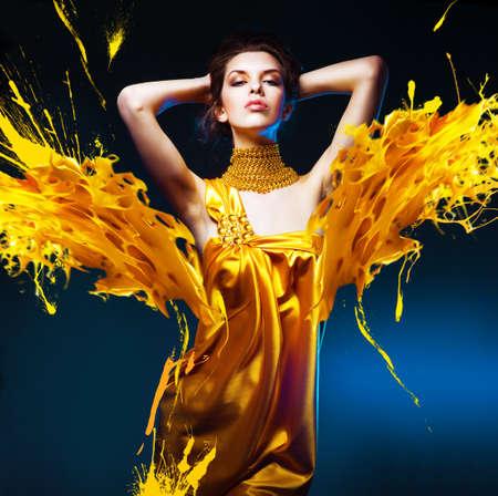 노란 드레스와 페인트 얼룩에 관능적 인 매력적인 여자