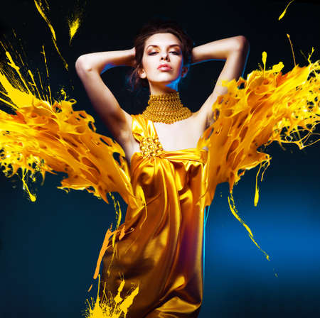 sensual attractive woman in yellow dress and paint splash