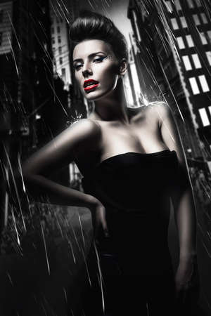 sexy brunette woman with red lips in dark rainy city Stock Photo