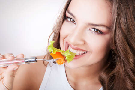 sexy smiling woman eating salad photo