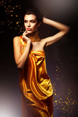 woman in long yellow dress and jewelry photo