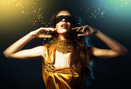 woman in yellow dress and mask with jewelry