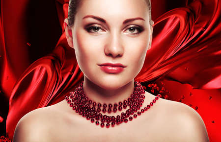 accessorize: beautiful woman with accessorize on red fabric background Stock Photo