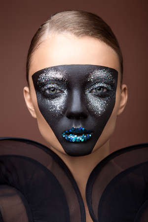 vibrance: Headshot of a woman with triangle black make-up and tinsel