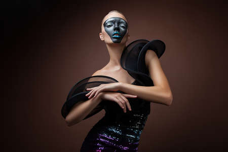 pretty woman in black dress with mask photo