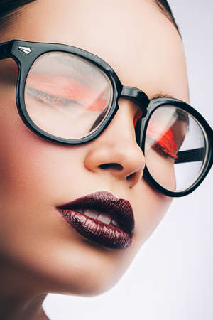 woman in glasses with orange make-up