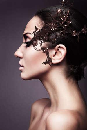 a brunette woman head profile with chocolate splash photo