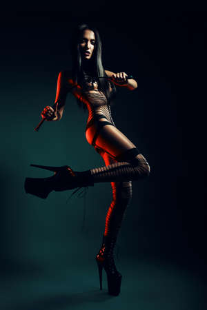 bdsm woman with whip in red light