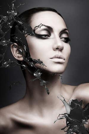 close up portrait of calm brunette woman black splash Banque d'images