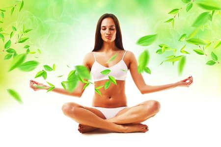 desnudo artistico: atractiva morena mujer en pose de yoga y hojas Foto de archivo