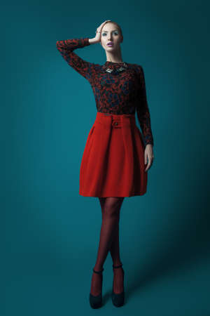 Elegant woman in red skirt on blue background photo