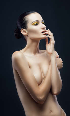half nude: Shot of a young nude woman with yellow make up