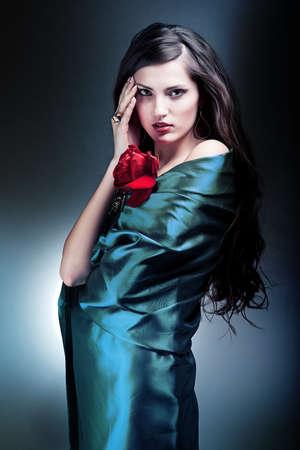 semblance: donna attraente in tessuto verde con rosa rossa