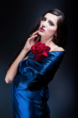 woman in blue fabric with red rose