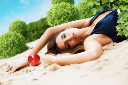 woman with red apple lays on sand in garden photo